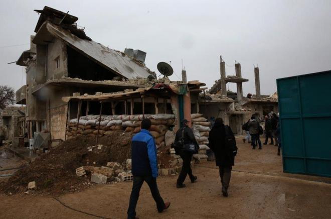 トルコ側から緩衝地帯を抜けて、シリア側の国境ゲートを歩いて超える報道陣。土のうが積み上げられ、クルド人の民兵組織が警備していました。建物は空爆や戦闘の被害を受け、激しく破壊されています。