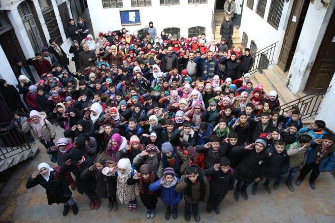 再開したアレッポ旧市街の小学校で国歌を歌う児童たち。この時、砲撃のような音が聞こえましたが、子どもたちは歌い続けていました