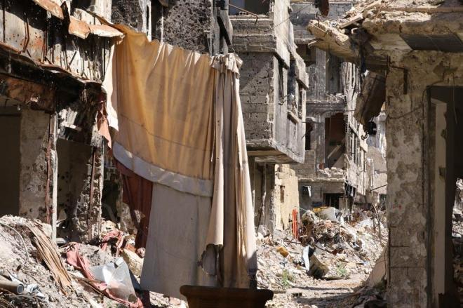 「カーテンの向こうにはISのスナイパーがいます」。同行したシリア情報省職員が言う。2015年5月、シリアの首都ダマスカス郊外にある「ヤルムーク難民キャンプ」の大部分は過激派組織「イスラム国」(IS)などが支配していました。難民キャンプといっても集合住宅が連なる普通の町並み。政府側との戦闘で建物は崩れ、外壁には焼け焦げた跡が残っていました。