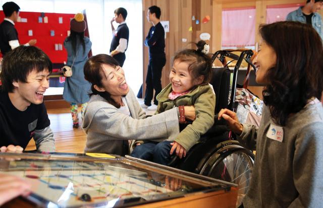 「やったね」。ピンボールに挑戦した杉本蓮ちゃん(7)は、かけられた言葉に笑顔で応えた。秋祭りのこの日、地域のボランティアや高校生が集まり、子どもたちを楽しませた=2016年11月6日、大阪市鶴見区