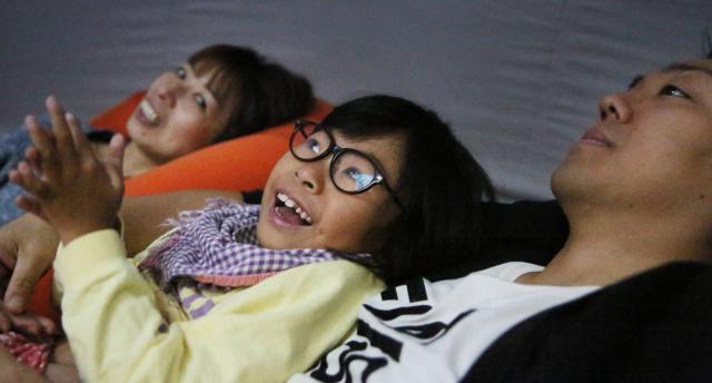 移動式プラネタリウムで両親とともに星空を観賞する女の子=2016年11月13日、大阪市鶴見区