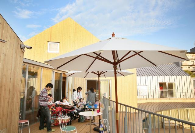 2階のバルコニーでくつろぐ子どもたち。建物には台所、音楽室、学習室、家族風呂などがあり、もう一つの「家」として自由に過ごせる空間になっている=2016年10月30日、大阪市鶴見区