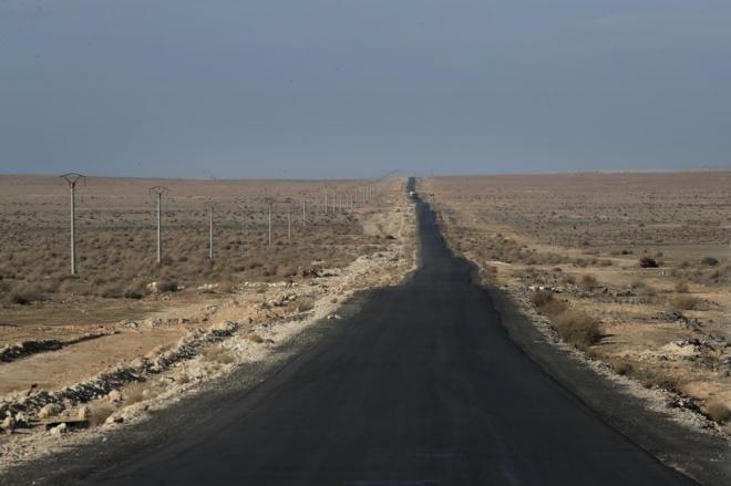 アレッポまであと100キロ。きれいに舗装された一直線の道路が続きます。左側には真新しい送電線と電柱がありますが、まだ工事中とのこと。周辺は砂漠が広がっています