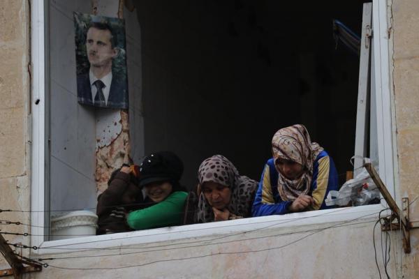 アレッポ東部のマサケン・ハナノ地区で避難生活を送る人々。アサド大統領の写真があった=2017年1月9日、シリア、矢木隆晴撮影