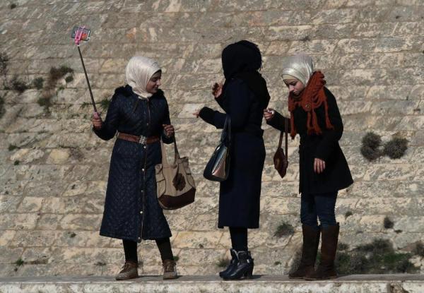 アレッポ城の塀に立ち、スマートフォンで自撮りする女性たち=2017年1月10日、シリア・アレッポ、矢木隆晴撮影