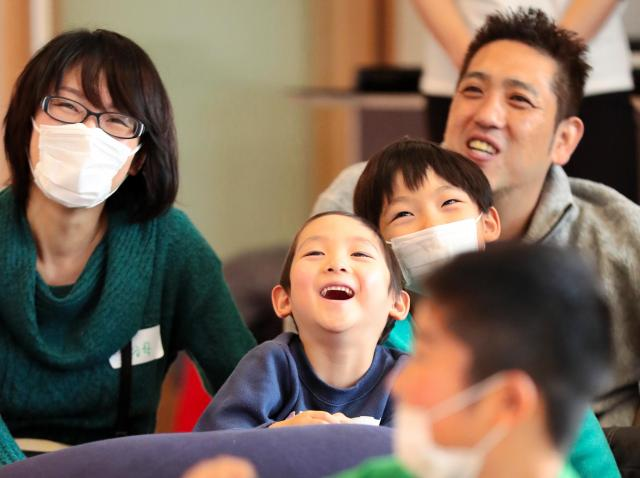 クリスマス会で、クラウン(道化師)のショーに笑顔になる家族=2016年12月17日、大阪市鶴見区