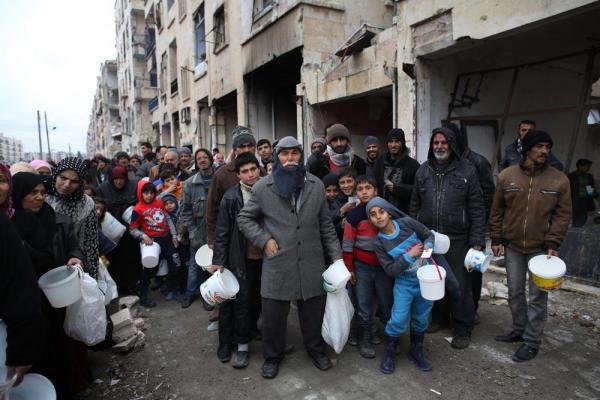 白いバケツやビニール袋を手に、食料の配給を受け取るため列を作る人々=2017年1月9日、シリア・アレッポ、矢木隆晴撮影