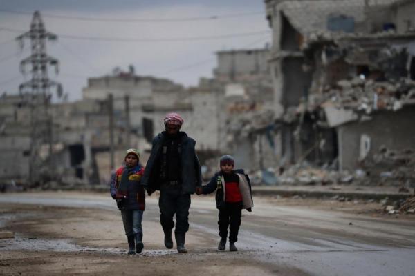 アレッポ東部で父親と思われる男性が子どもの手を引いて歩いていた=2017年1月9日、シリア・アレッポ、矢木隆晴撮影