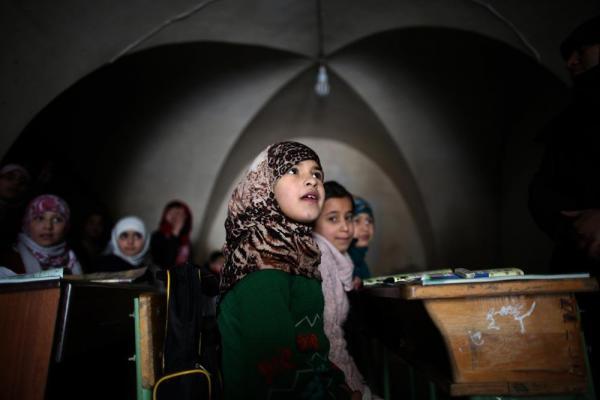 再開されたアレッポ東部のサータ・アルフサリ小学校。明かりがない部屋で子どもたちが勉強していた=2017年1月10日、シリア・アレッポ、矢木隆晴撮影
