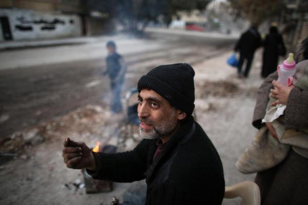 ザブディーヤ地区の自宅に戻った男性。路上で暖をとっていた=2017年1月11日、シリア・アレッポ、矢木隆晴撮影