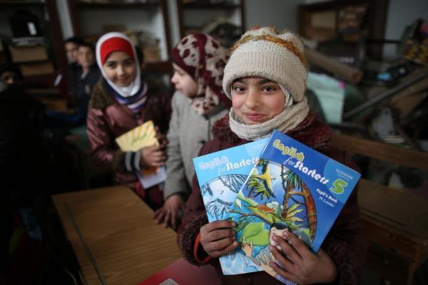 再開されたアレッポ東部のサータ・アルフサリ小学校で、英語の教科書を手にする子どもたち=2017年1月10日、シリア・アレッポ、矢木隆晴撮影
