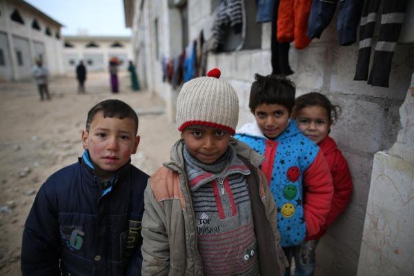 アレッポ東部ジブリーン地区にある、元は倉庫だった建物で避難生活を送る子どもたち。壁には洗濯物が干してあった=2017年1月9日、シリア、矢木隆晴撮影