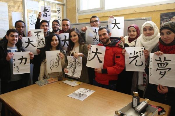 自分たちで書いた習字を掲げるアレッポ大学の学生たち=2017年1月11日、シリア・アレッポ、矢木隆晴撮影