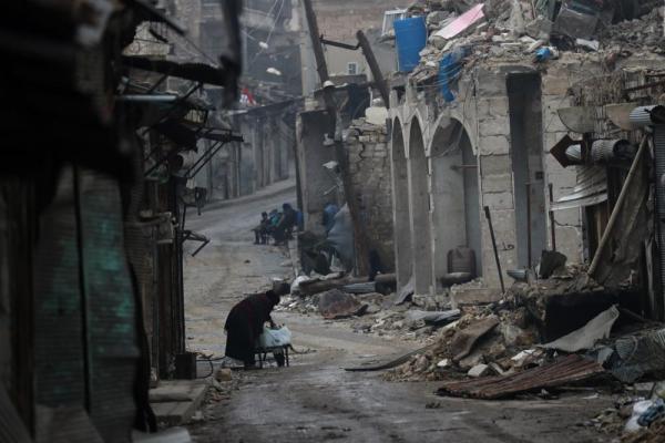 激しい戦闘で建物が破壊されたアレッポ旧市街。女性が台車で水を運んでいた=2017年1月10日、シリア、矢木隆晴撮影