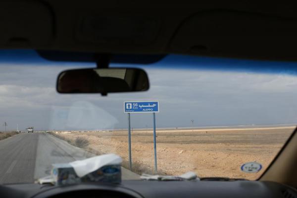 車から「アレッポまで56㌔」の標識が見えた=2017年1月8日、シリア、矢木隆晴撮影
