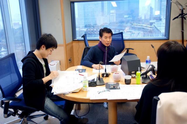 時折、携帯電話でツイッターを見ながら番組を進める吉田照美さん(奥)=2011年12月8日、東京都港区