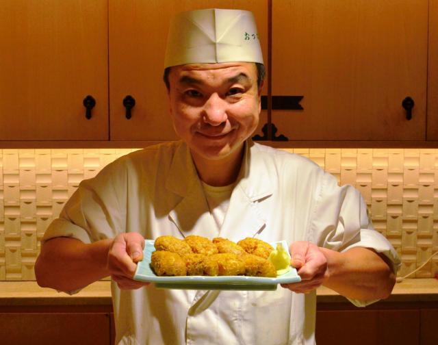 「おつな寿司」のいなりずしを手にする店主の近藤功夫さん=東京都港区