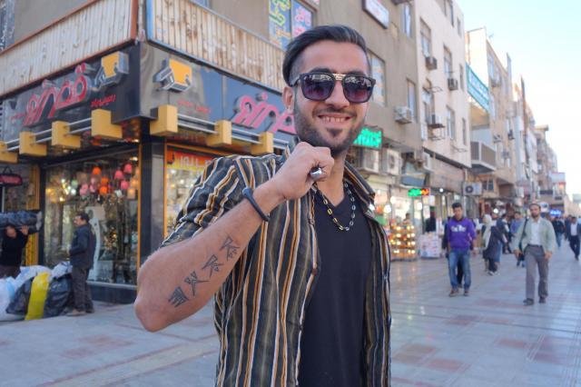 腕のタトゥーを誇らしげに見せるイラン人男性
