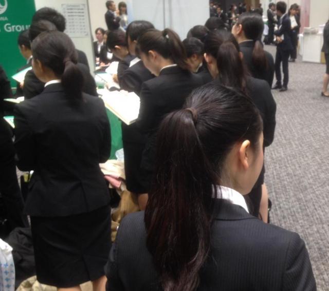 黒いリクルートスーツで企業の説明を聞く学生たち=東京都新宿区