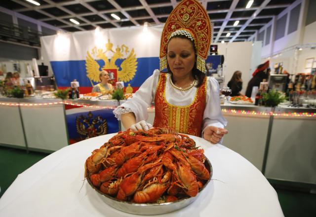ベルリンであったロシアの伝統料理フェスティバルでザリガニ料理を披露する女性=2016年1月