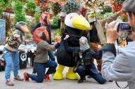 身も心も鳥になりきって記念撮影を楽しむ鳥好きたち。オニオオハシをモチーフにした松江市の花鳥園「松江フォーゲルパーク」のマスコットキャラを囲んだ