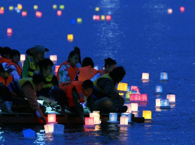 石巻の川開き祭りでは、東日本大震災の犠牲者の鎮魂を願い、次々と灯籠(とうろう)が流された=2011年7月31日