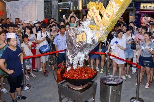 湖南省長沙市で掘削機が1000匹のザリガニを炒める様子を見つめる人たち=2015年7月