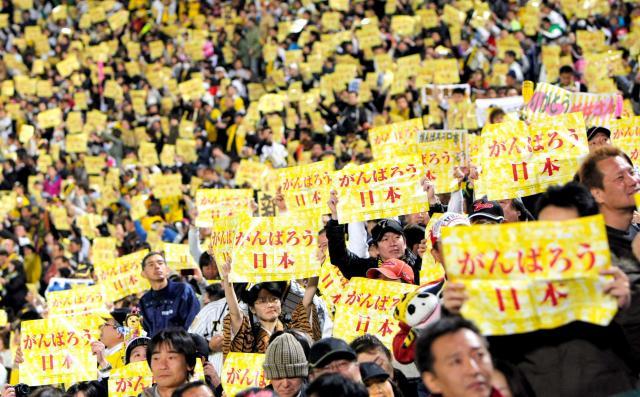 「がんばろう日本」と書かれた紙を掲げて声援を送る阪神ファンたち=2011年4月12日、阪神甲子園球場
