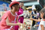 皮ごと丸かじりしてもおいしいという特産の桃「あかつき」を配って福島の復興をPRするミスピーチ(左)ら=2013年8月3日、JR京都駅