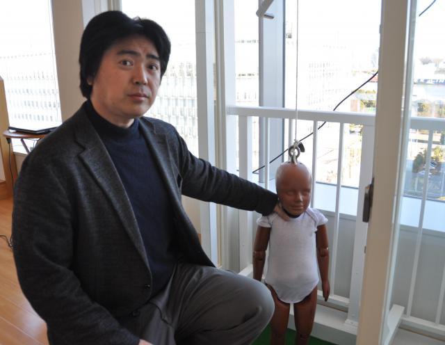 産業技術総合研究所の西田佳史さん。職場には様々な実験のために住居を再現した「人工知能研究センター リビングラボ」があり、実験用のダミー人形が置かれている=東京都