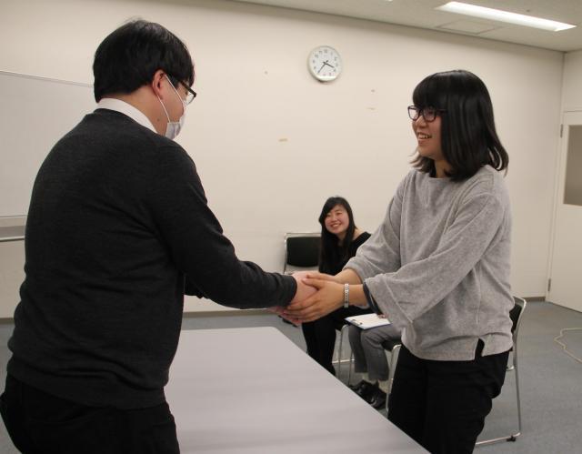 握手会のシミュレーションをする学生(右)。阪本記者がドルヲタ役