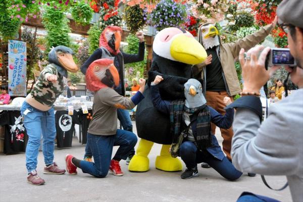 身も心も鳥になりきって記念撮影を楽しむ鳥好きたち。オニオオハシをモチーフにした園のマスコットキャラクターを囲んだ。