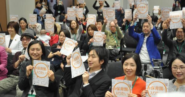 「#保育園に入りたい!」と書かれたチラシを掲げる参加者たち=2017年3月7日、東京都千代田区の衆議院第2議員会館