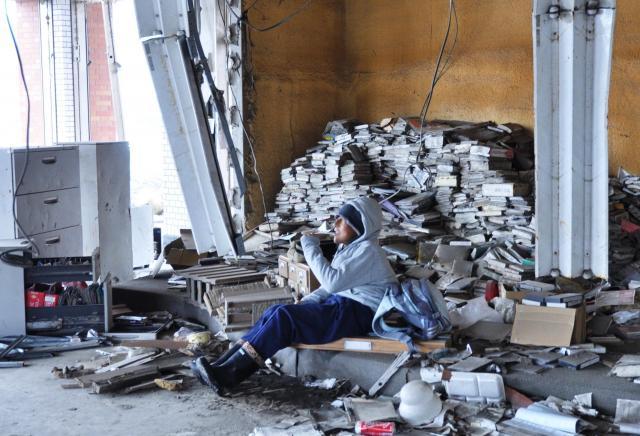 震災から1年が経った被災地を取材時に、津波で本が散乱した図書館の中で突然歌い始めた男性。「カラオケしたいよ」とつぶやいた姿が忘れられない=2012年3月、岩手県大槌町