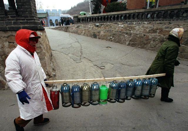 出稼ぎ労働者がお湯を運ぶ様子=1997年12月、北京八達嶺