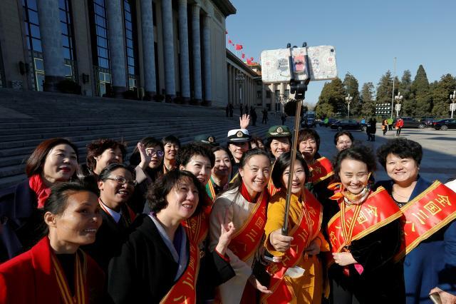 全人代の女性代表たちが「国際女性のデー」のために自撮り写真を撮る=2017年3月7日、北京