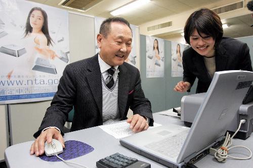 パソコンで申告書を作るシステムを体験する板東英二さん=2006年2月16日