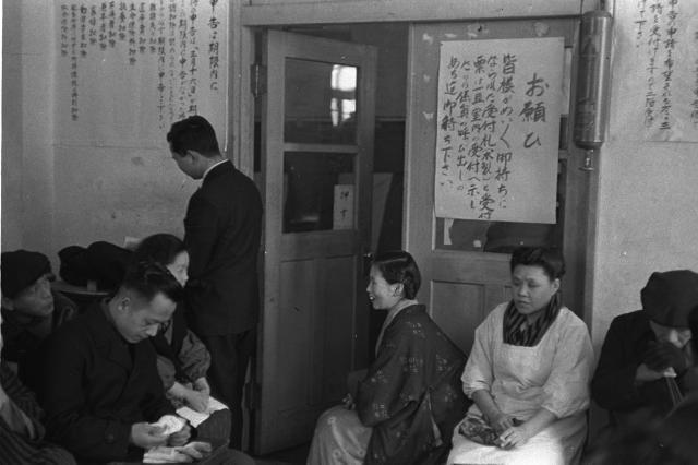 1953年の確定申告の風景。受け取った木札を持って係員の呼び出しを待っている申告者=浅草税務支所