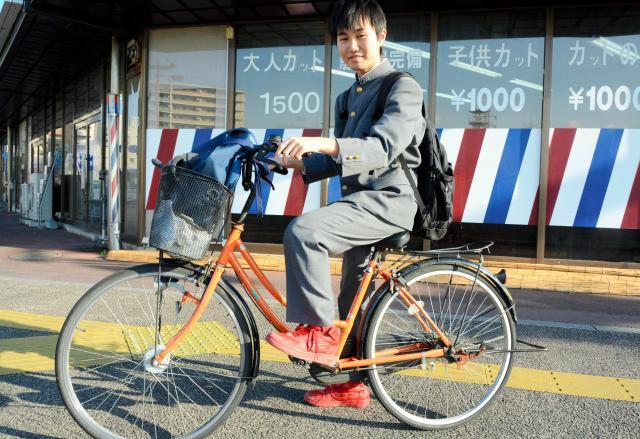 オレンジの自転車に乗る高校生。靴の色とも合っている=佐賀市天神2丁目