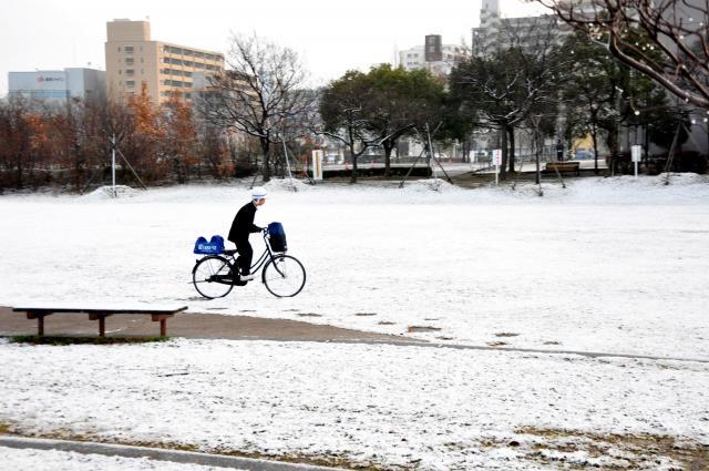 佐賀市天神の「どんどんどんの森」で薄く積もった雪の上を自転車に乗って通学する生徒=2013年1月18日