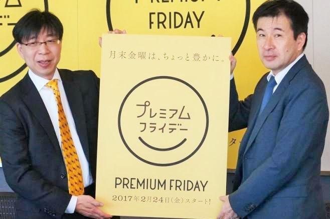 「プレミアムフライデー」のロゴマークを掲げる男性