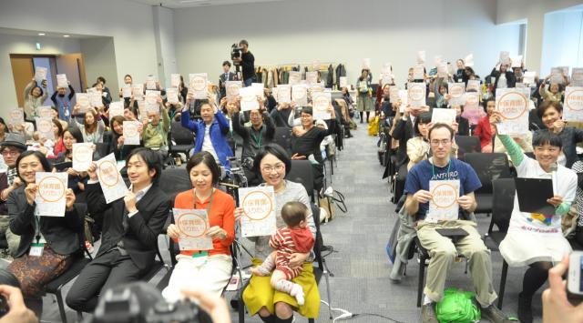 「#保育園に入りたい!」とのチラシを掲げる参加者たち=2017年3月、東京・永田町
