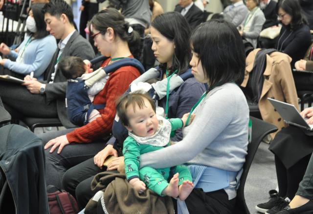 赤ちゃんを抱きながら、話を聞くイベントの参加者たち=2017年3月、東京・永田町