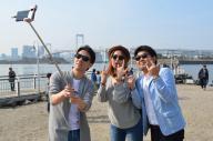 「リア充アピール代行」サービスのゆうくん(左)、えりちゃん(中央)と写真を撮る記者(右)=東京都港区