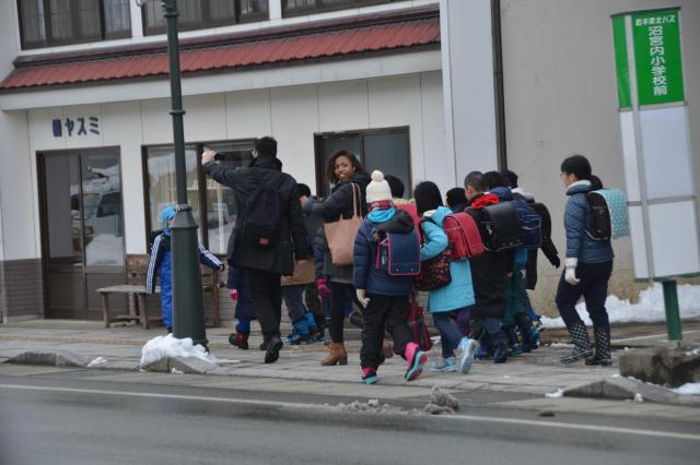 岩手町の商店街を散策中のロレッタさんとシャルルさん。物珍しさに下校中の子どもたちがぞろぞろと、ハーメルンの笛吹き状態