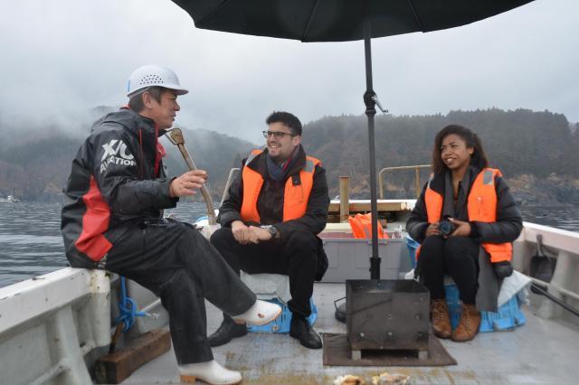 大船渡市でホタテ漁師の佐々木淳さん(左)の船に乗船したロレッタさん(右)とシャルルさん。震災後、漁を復活させるまでの話に聴き入る