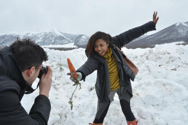 雪の下から収穫したニンジンを手にポーズ。ロレッタさんの撮影風景