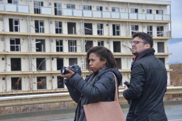 津波で被災した陸前高田市の集合住宅。町に正午を告げる音楽が流れる様子を撮影するロレッタさん(左)とシャルルさん