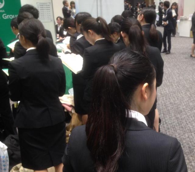 黒いリクルートスーツで企業の説明を聞く学生たち=3月、東京都新宿区
