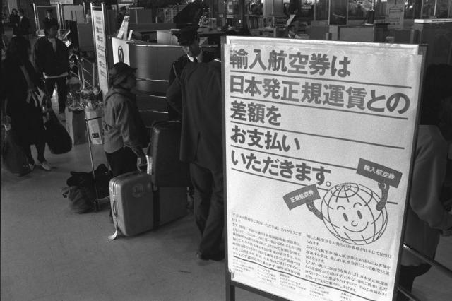 成田空港出発ロビーに立てられた「輸入航空券」の差額徴収を告げるポスター=1989年1月27日